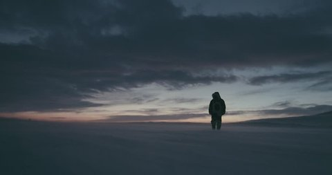 Young traveller dressed in traditional reindeer skin coat goes through a blizzard at beautiful sunset. Polar expedition 2016. Red Epic 4k resolution. HD
