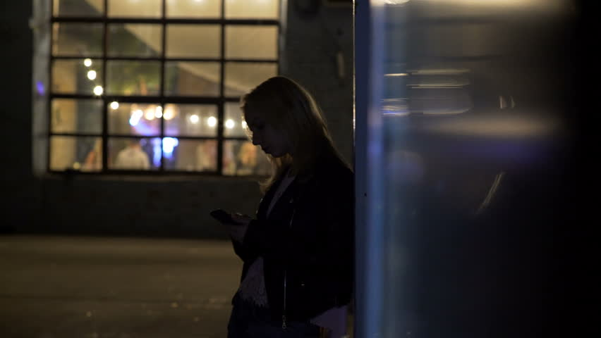 Lonely girl standing on alley near nightclub and calling taxi, night life #22632064