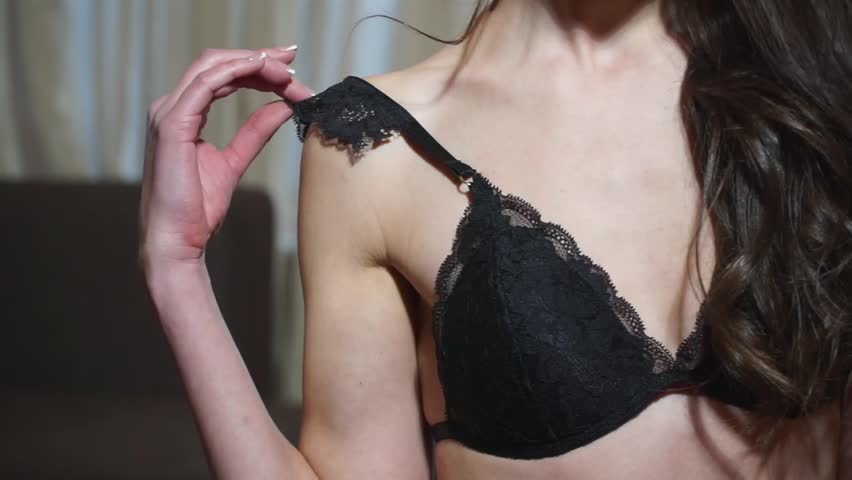 Close-up, chest, hot sexy girl gently pulls strap black lace bra