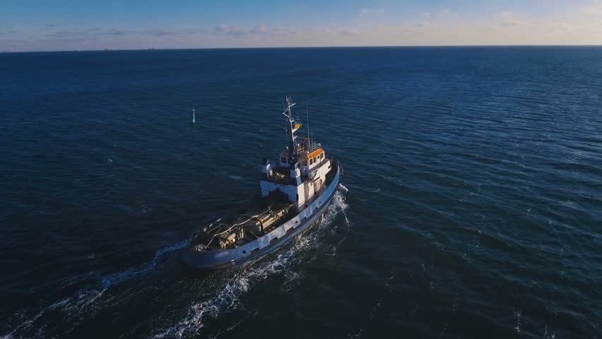 The towboat leaves from the port to meet a giant cargo ship. Aerial shooting. 4K