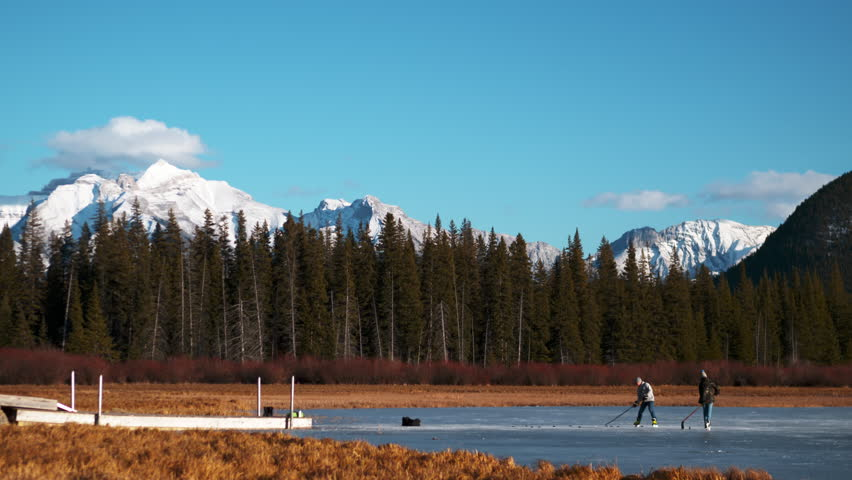 People ice skating and playing hockey on a pond in the Canadian Rocky Mountains.  Vermilion Lake in Banff National Park, Alberta Canada.
