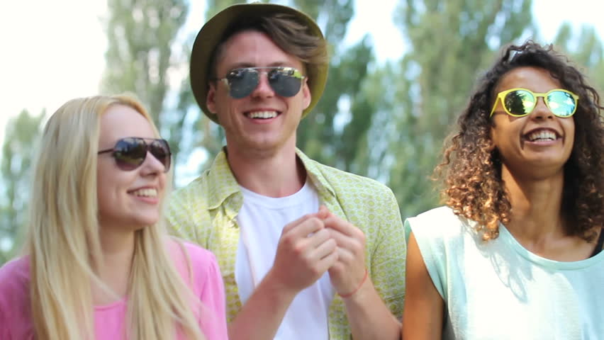 Young couples enjoying their time at music festival, singing, dancing together