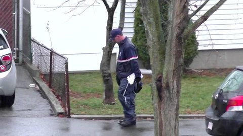 Post office mailman delivers in rainy weather - Revere, Massachusetts USA - Dec. 23, 2016