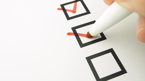 Male hand putting mark on checkboxes of checklist