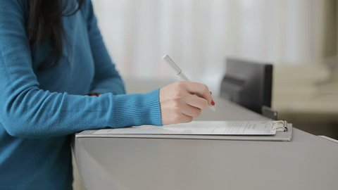 Young girl fills form for patients in the dental clinic