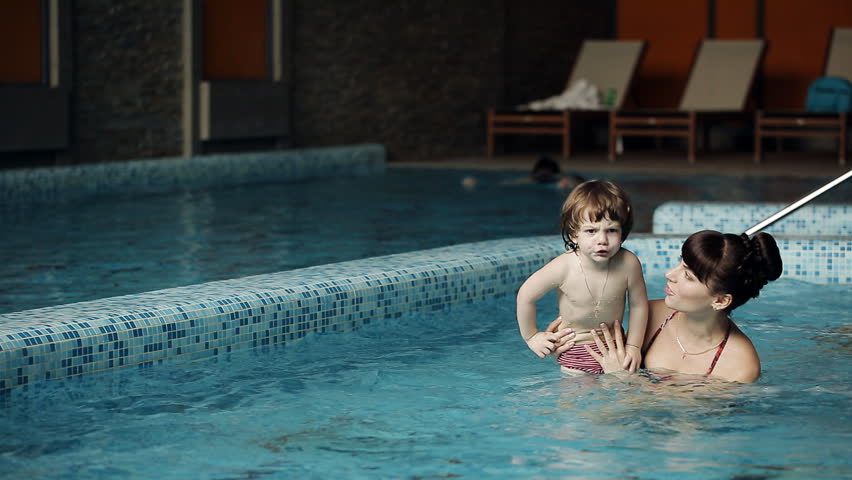Cute Blonde Toddler Is Diving Under The Water While His Mother Holding Him