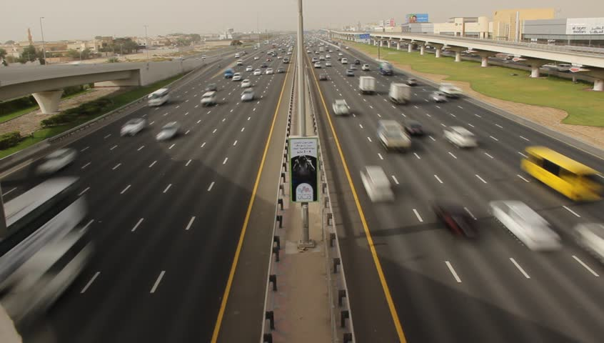 DUBAI, UAE - JUNE 03, 2013: Nonstop traffic at Sheikh Zayed road, time lapse from above carriageway. Symmetric perspective, wide angle shot of inter-city arterial highway. Seven lane in each direction