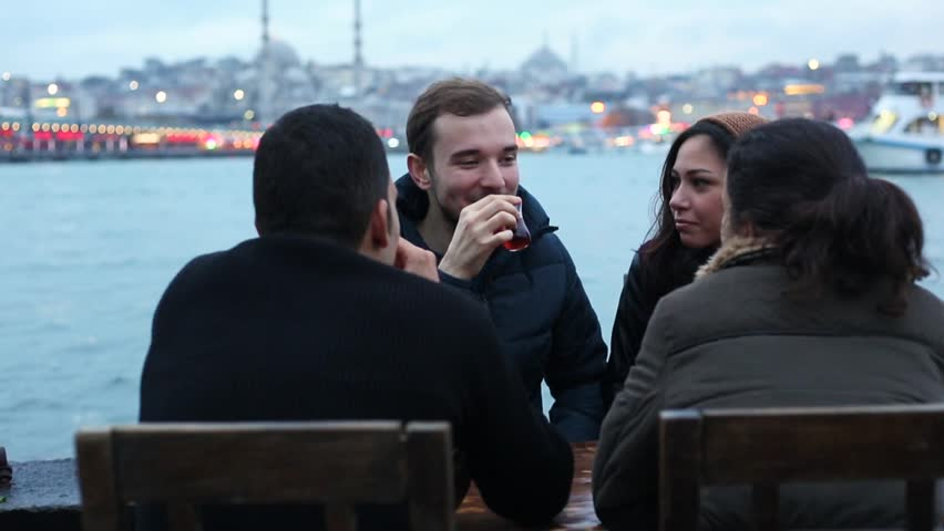 Group of Turkish friends drinking cay, traditional tea in Turkey. They are two boys and two girls sitting by the river in Istanbul. Friendship and lifestyle concepts.