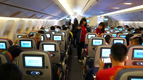 MOSCOW - APRIL 01, 2015: Plane captain loud speaker announce during flight, say that airliner approaching and will land soon. POV walk through economy class cabin aisle, full of Chinese travellers
