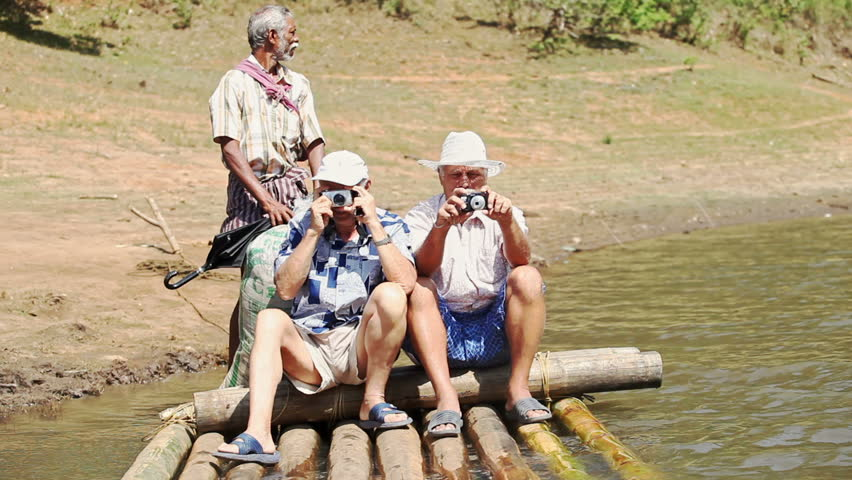 PERIYAR, KERALA/INDIA - FEBRUARY 12 2012: Caucasian tourists two old men sit on large wooden raft photo landscape Indian man rows in tropical national park on February 12 in Periyar
