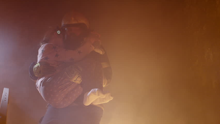 Brave Fireman Descends Stairs of a Burning Building with a Saved Girl in His Arms. Shot on RED Cinema Camera in 4K (UHD).
