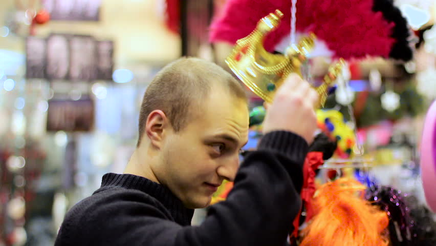 Pretty young man wearing crown and smiling to the camera
