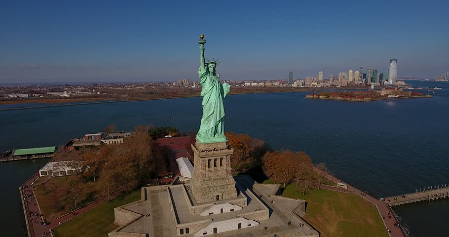 The Statue of Liberty, with the New York City skyline and Ellis Island in the background.   Shutterstock HD Video #22794214