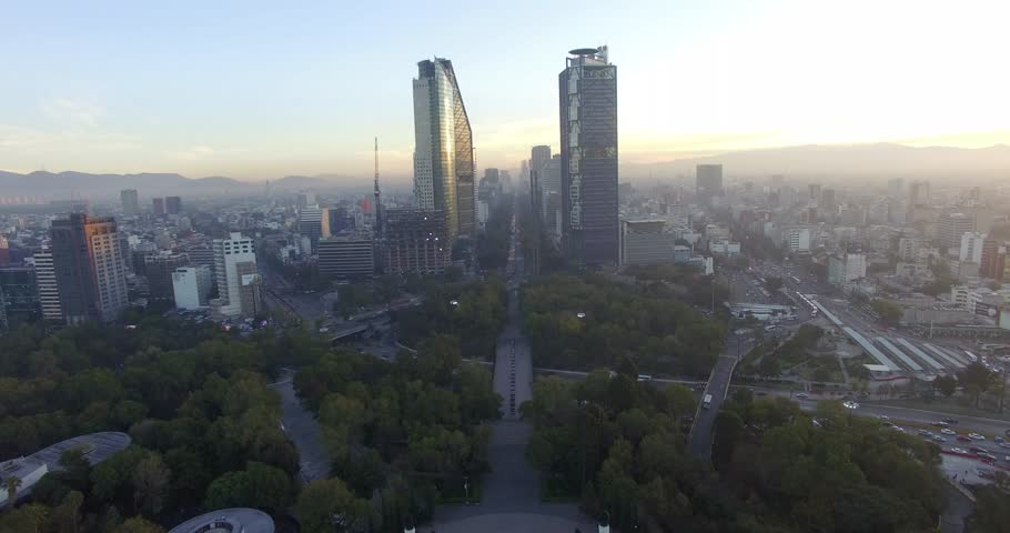 This wide forward dolly drone shot shows the Mexico City skyline and traffic early in the morning.