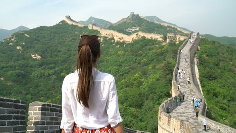 Happy cheerful tourist woman at Great Wall of China having fun free in freedom pose with arms up on travel during vacation trip in Asia. Girl visiting and sightseeing Chinese attraction in Badaling