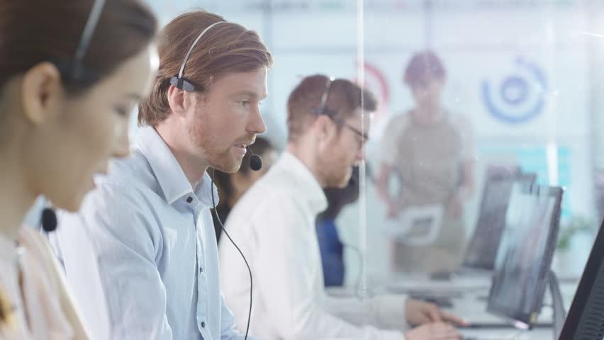 4K Friendly customer service operators taking calls in busy call center Dec 2016-UK | Shutterstock HD Video #22933954