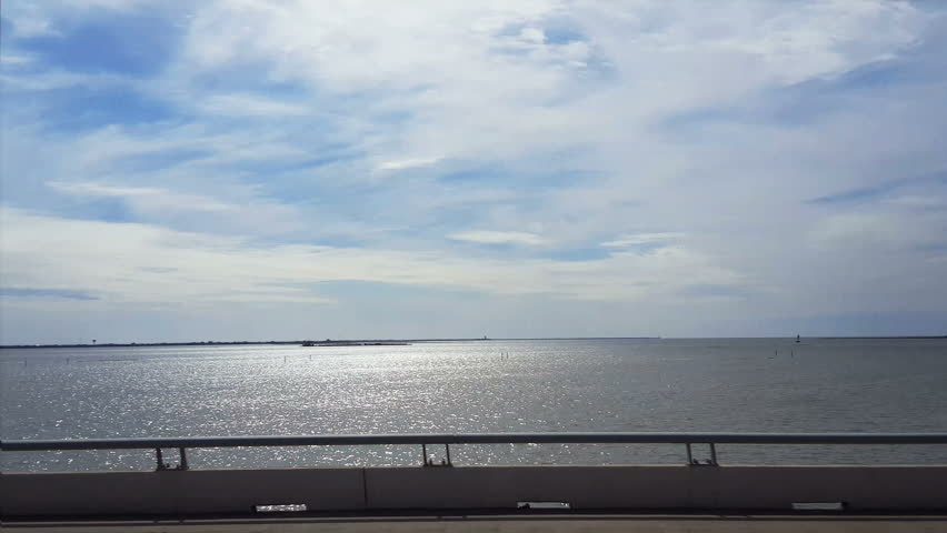 POV-Passenger side window driving Interstate 45 causeway to Galveston, Texas Island with filtered sunlight reflecting off the inland waterway and high wispy clouds against a blue sky.