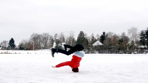 Young man dancing breakdance on a frozen pond in winter.