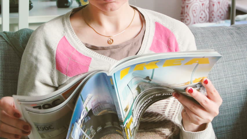 PARIS, FRANCE - CIRCA 2015 Turning pages of magazines - woman reading IKEA Catalogue before buying furniture new house in France. The catalogue is published annually by the Swedish furnishing retailer