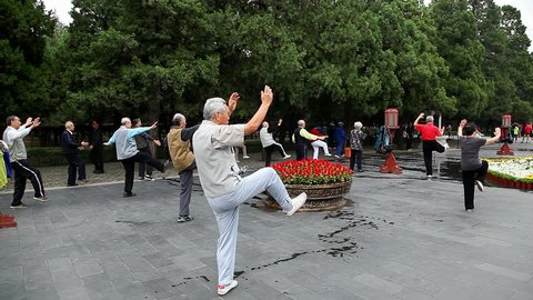 BEIJING, CHINA - SEPTEMBER 27, 2014: Chinese group of old senior people practice Tai chi Chuan Taijichuan exercise in a public park on September 27, 2014 in Beijing, China