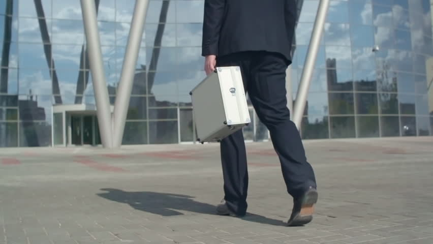 Tracking of legs of businessman holding money case and walking towards building | Shutterstock HD Video #22972744