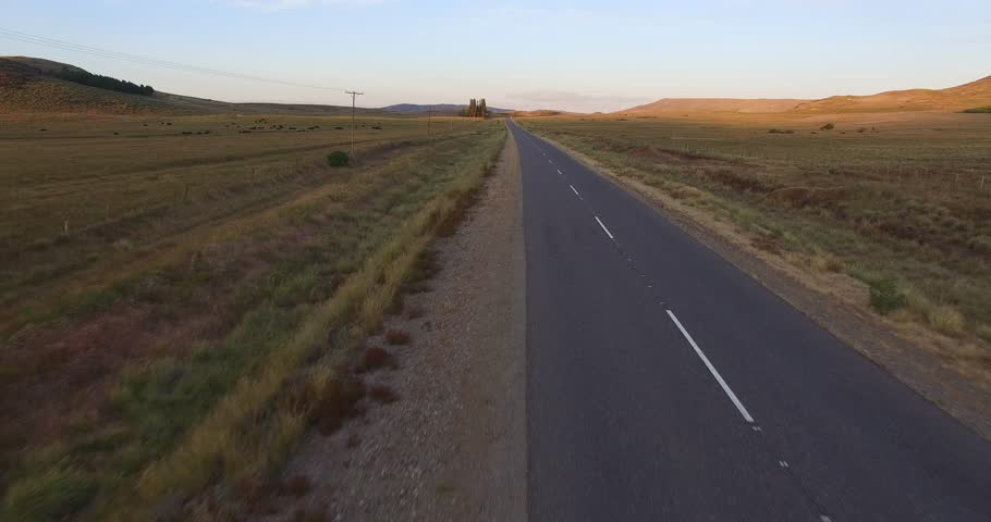 Aerial drone scene of sunset in Patagonia, Argentina. Steppe landscape. Camera moving back very fast and getting close to the floor. Route texture detail. | Shutterstock HD Video #22980304