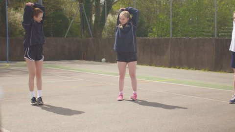 4K Young netball team on outdoor court warming up before a game Dec 2016-UK