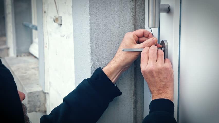 Intruder Or Burglar With Lock Pick Tool Opens The Front Door To ...