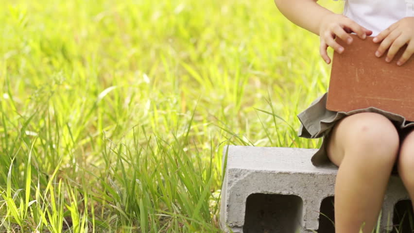Girl in hard hat sitting on cinder block gives thumbs up | Shutterstock HD Video #2299184