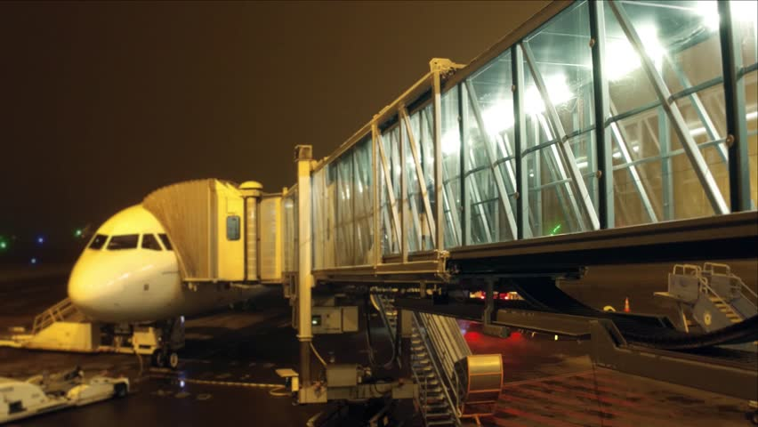 Passengers boarding airliner using glass jet bridge at night. Travel, departure, leaving concepts. 4K video