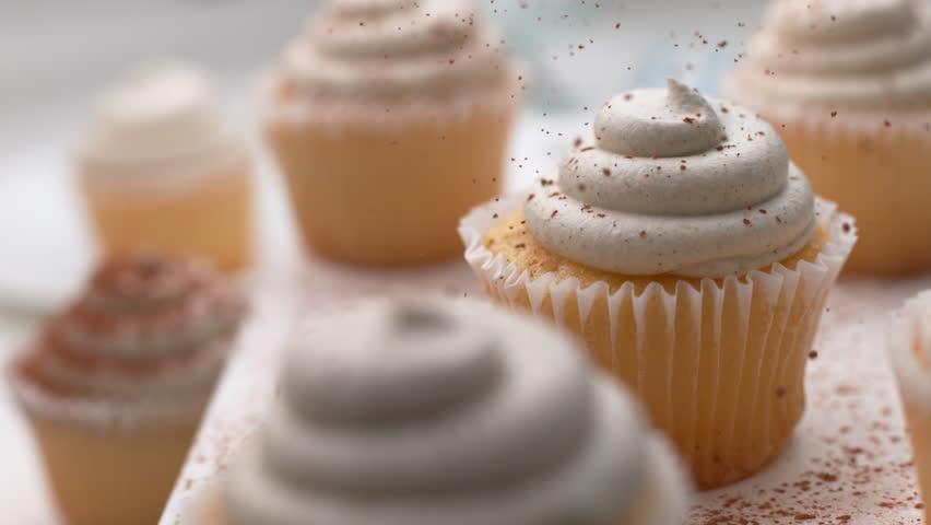 Cinnamon sprinkled onto vanilla cupcakes in super slow motion, shot on Phantom Flex 4K