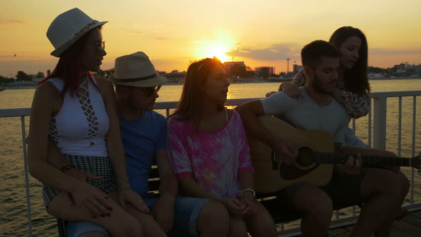 Group of friends sitting on a bench and singing with a guitar at sunset on a pontoon | Shutterstock HD Video #23040724