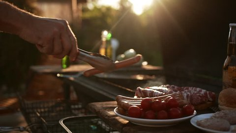 Man's hand puts sausages and meat on barbecue grid outdoors while sun shinning in slowmotion