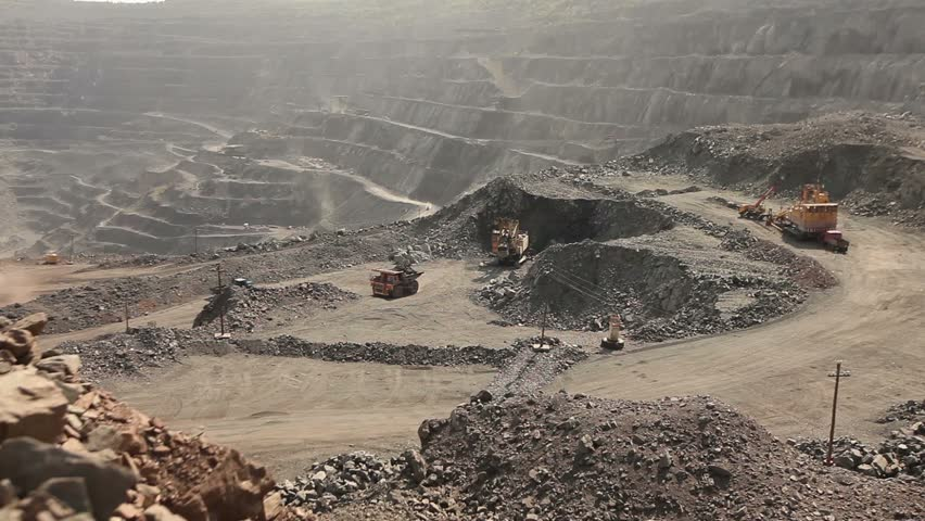 Open pit iron ore mining, a big yellow mining truck at work, working in a quarry, big yellow heavy truck in open cast mine, mining of iron ore, view from above, Dump Truck, sunny day  | Shutterstock HD Video #23050594