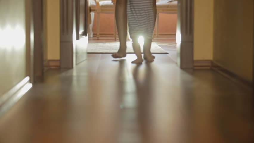 Closeup of mothers and baby's feet walking on wooden floor at long hallway