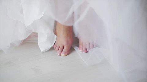 Female feet with neat polished pedicured toe nails close up. No face woman sit or stand barefoot at floor detail. Hem of dress or skirt shallow dof. Cinderella style glamour girl going to wed or ball