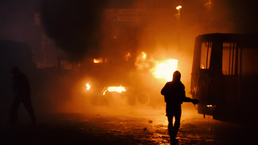 Kiev, Ukraine, January 2014: Protester throws a stone in the direction of the burning bus. During the protests against President Yanukovych in Kyiv on the street Grushevskogo January 19, 2014
