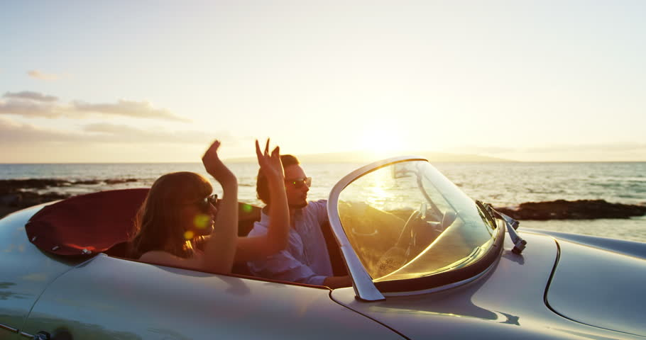 Happy Couple Driving into Sunset in Classic Vintage Sports Car by the Ocean. Romantic Sunset Drive. Shot on RED   Shutterstock HD Video #23083648