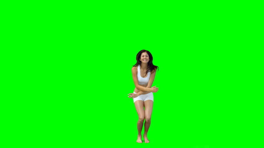Dark haired woman jumping into the shape of an x against a green screen
