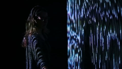 ABRAU-DURSO, RUSSIA - September 11, 2016: Girl play with interactive video installation. A new kind of art, generative graphics. Audio-visual exhibition in MARS Center, ABRAU-DURSO