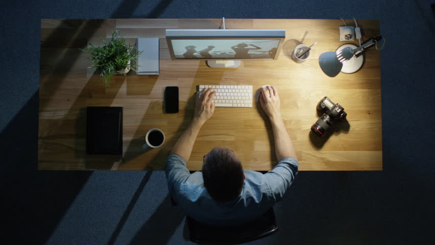 Top View of a Young Photographer Processing Photographs on His Desktop Computer Late at Night. Table Lamp Illuminates His Desk. Camera, External Hard Drive and Notebook Lie Beside Him.   Shutterstock HD Video #23115988