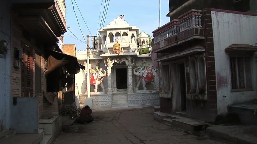 narrow street with temple at end as bicycle passes by, Ghanero, Rajasthan, India