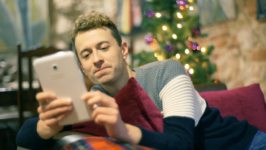 Man browsing internet on tablet and smiling to the camera in the festive cafe, steadycam shot  | Shutterstock HD Video #23117344