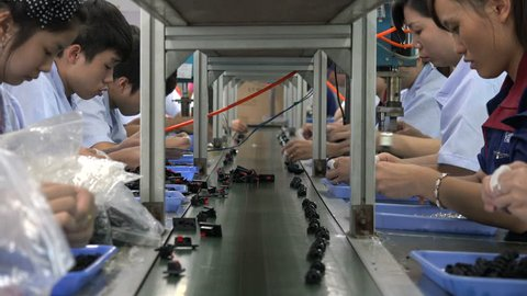 SHENZHEN, CHINA - 16 NOVEMBER 2016: Employees of an electronics factory work on the conveyor belt in Shenzhen, China