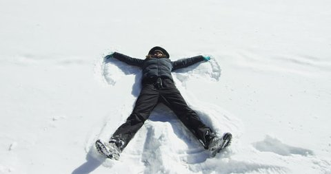 A mountain girl plays snowballs, dive and do the angel and blowing snow in the room. Surrounded by nature plays like a child, concept: fun, play, vacation.