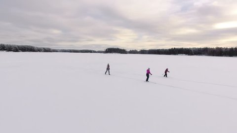 Camera flying around three sporty different ages female skiers running on cross-country ski. Frozen lake. Russia