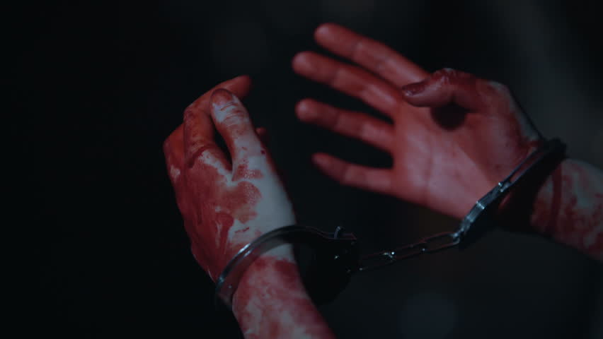 Close-up of bloody trembling murderer's hands in handcuffs, crime and punishment
