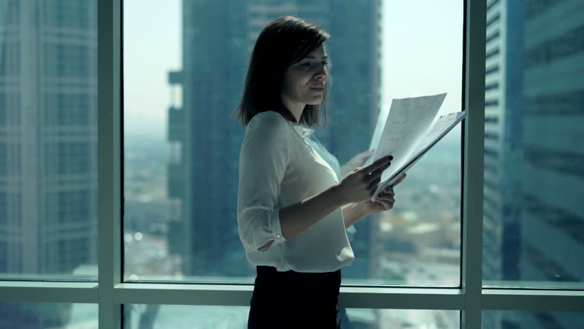 Young businesswoman working with documents standing by window in office  | Shutterstock HD Video #23137264