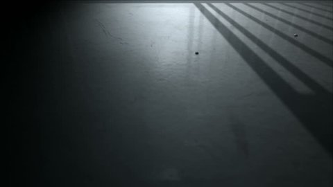 A 4K static camera closeup showing a dimly lit floor of a prison cell and the cast shadows of the door slamming shut