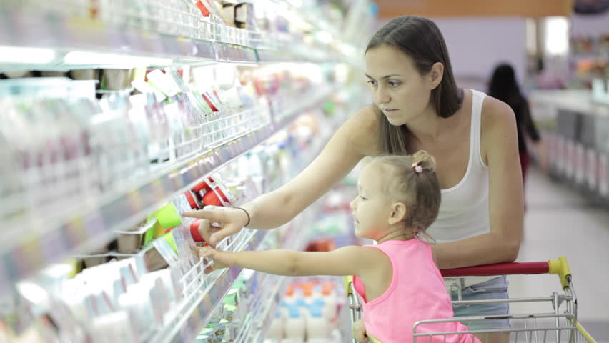 Young attractive woman with cute daughter in shopping cart choosing a yogurt in grocery section at supermarket | Shutterstock HD Video #23156314